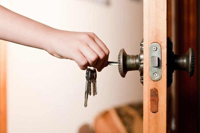 Locking up or unlocking door with key in hand