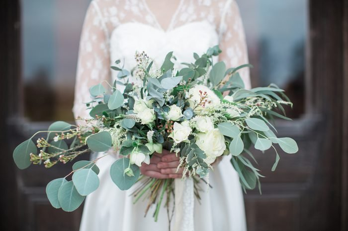 Handed wedding bouquet with roses and eucalyptus greenery.