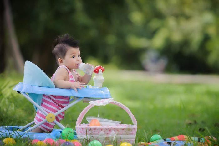 Cute baby drinking milk from a bottle in a baby walker, happily and relaxes in the garden,Important part of the family.