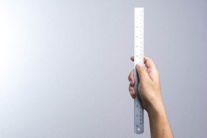 Hand holding a ruler on white background