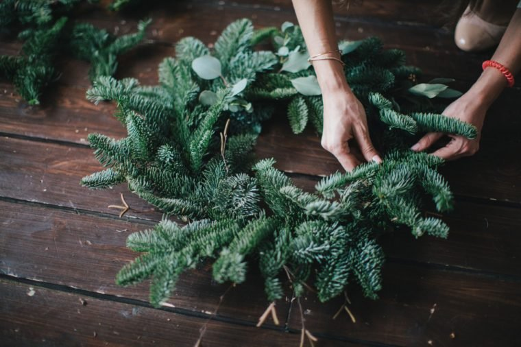 Woman making christmas wreath on a dark wooden table. Concept of florist's work before christmas holidays.