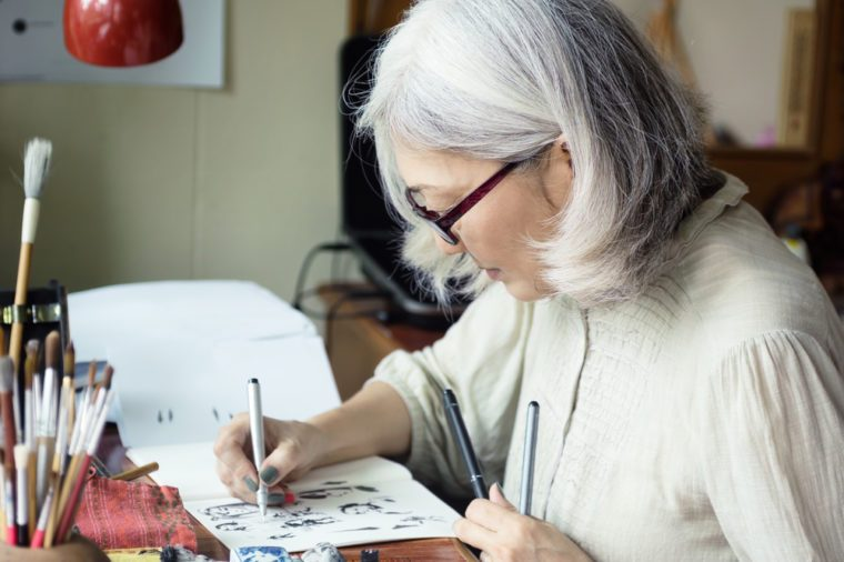 Asian senior woman artist sketching. Focus on face, blurred workspace in background. Art background, text space