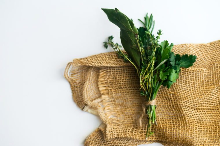 Bouquet garni with bay leaves and fresh herbs de provence on rustic towel on white background with copy space