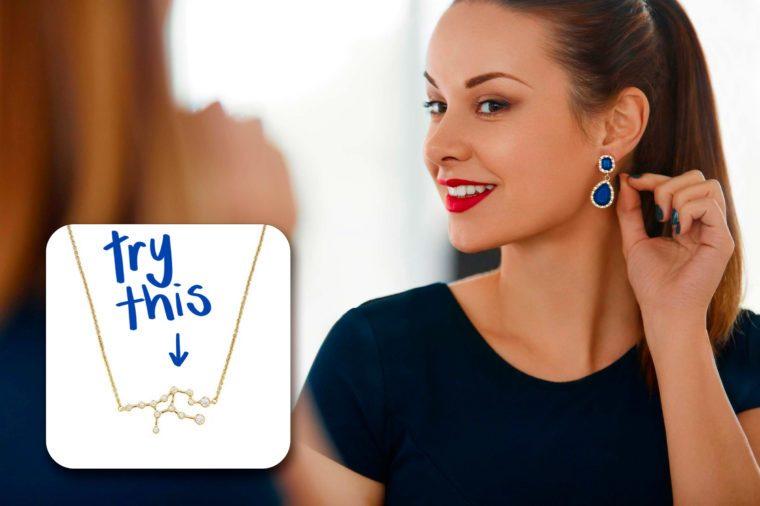 woman admiring her earrings in the mirror