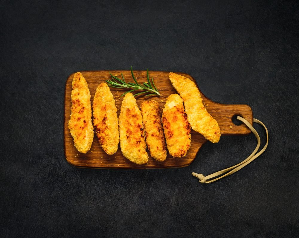 Top View of Baked Chicken Fingers Nuggets on Dark Background