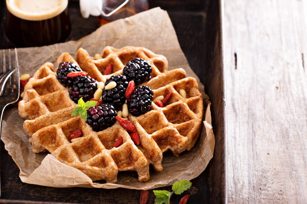 Whole wheat breakfast waffle served with blackberries and goji berries