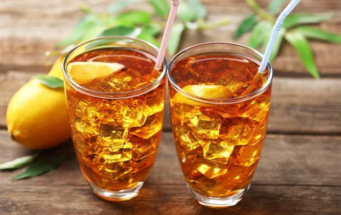 Two glasses of iced tea with lemon on wooden background