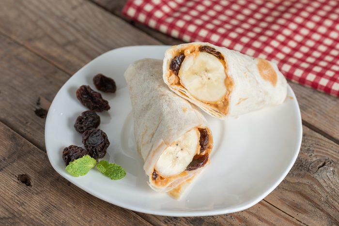 Slice tortilla wrap with peanut butter, raisin and banana.