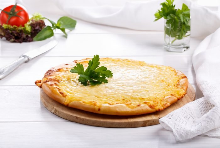 Flat bread with cheese. Whole flatbread pizza on white table.