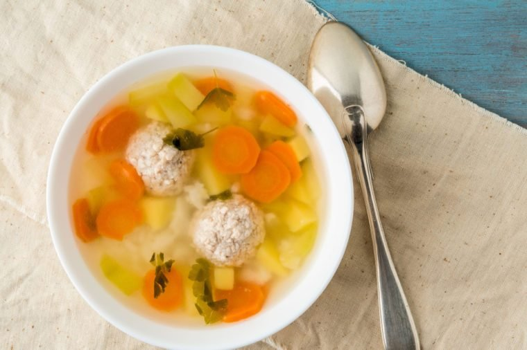 bowl of soup, a cup of broth and vegetables, meatballs made of turkey and chicken, top view