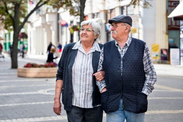 mature couple walking on street in autumn day