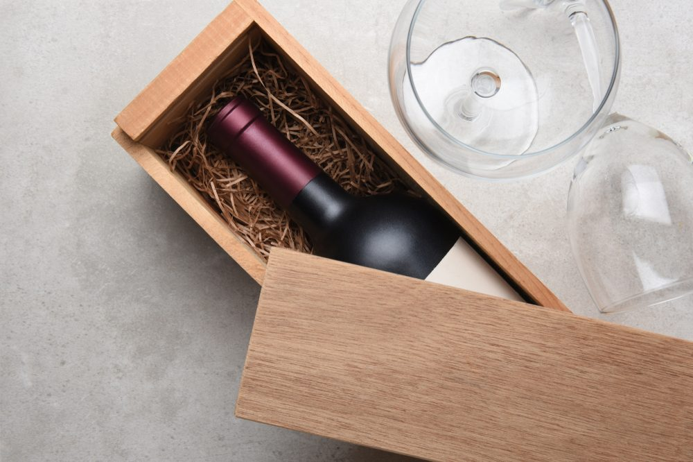 Red Wine Box: A single bottle of Cabernet in a wood box partially covered by its lid with two empty glasses.