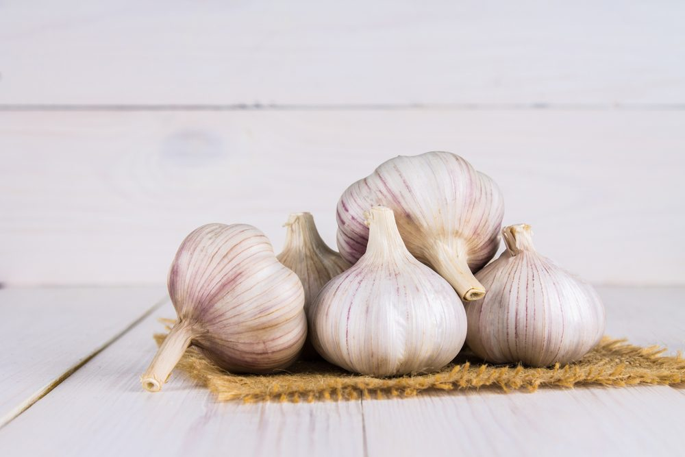Garlic cloves and garlic bulb on a white wooden table