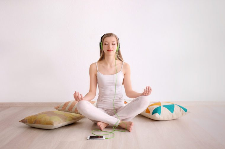 Young woman meditating and listening to music while sitting on floor at home