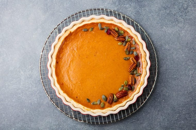 Tasty pumpkin pie, tart made for Thanksgiving day in a baking dish on a colling rack. Grey stone background. Top view.