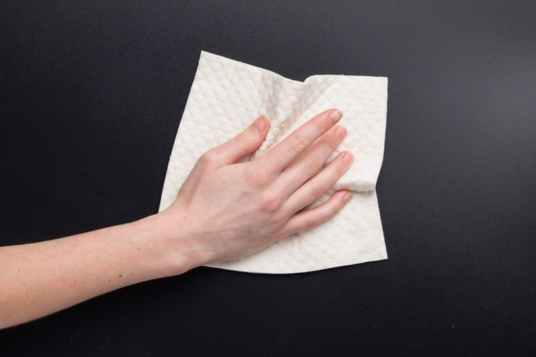 Hand hold dry cleaning cloth. Woman's hand clean kitchen black table