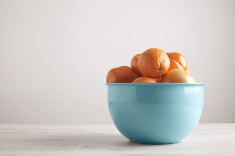 Different fruits and citrus in big metallic blue bowl in front of blank wall on white wooden table from side