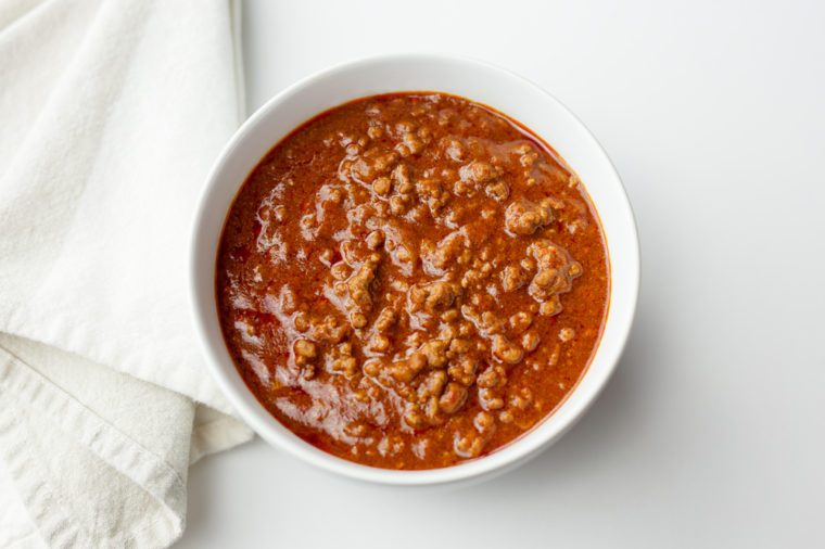 Bowl of chili with napkin on white background.