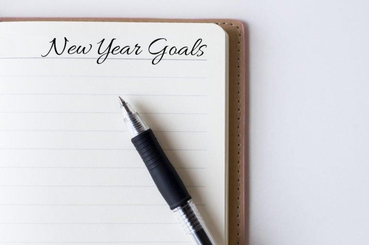 Conceptual,notebook on a white table. open diary and pen with new year goals words