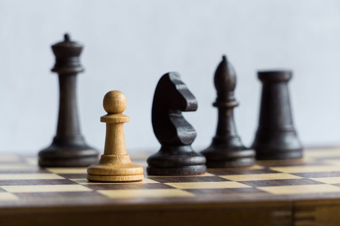 Black chess pieces pursuing a white pawn