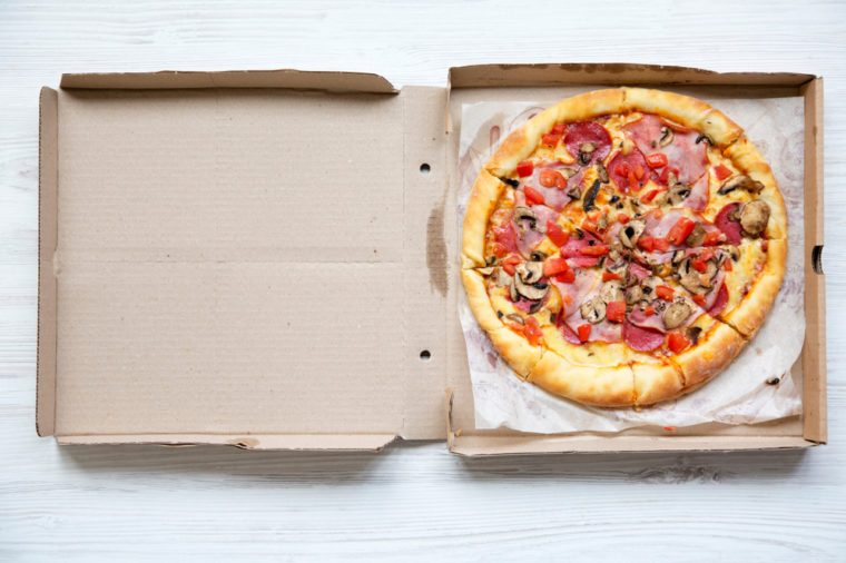 Fresh pizza in a cardboard box on white wooden table, top view. From above, flat lay.