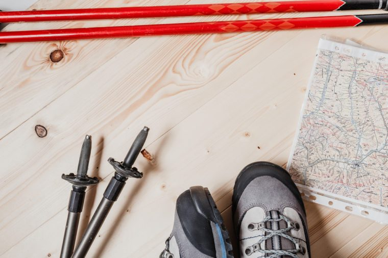 Accessories for the trekking on a light wooden background - shoes and hiking sticks