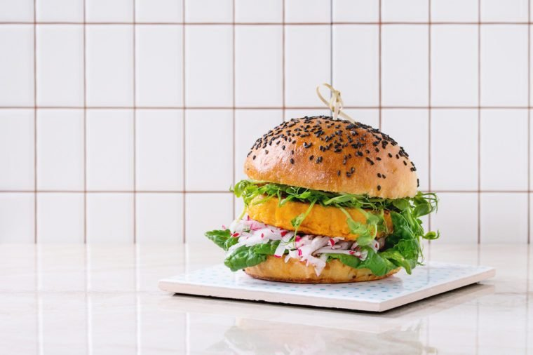 Homemade veggie sweet potato burger with fresh radish and pea sprouts served on ceramic board over white marble table with tile wall at background.