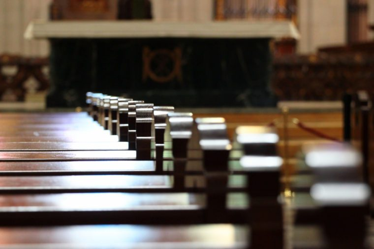 Rows of church benches. Sunlight reflection on polished wooden pews. Selective focus.