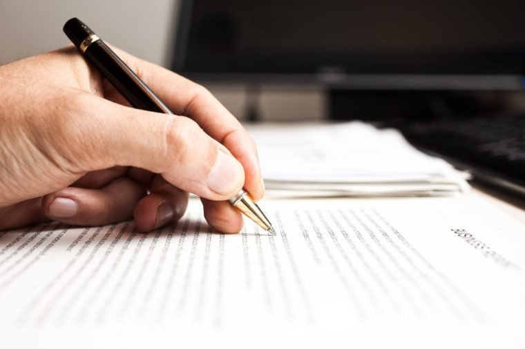 Closeup of a person writing on a document