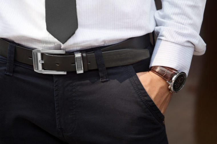Closeup shot of male waist with hand in pocket dressed in black pants, belt, grey shirt, black tie and watch with brown watch strap. Formal wear.