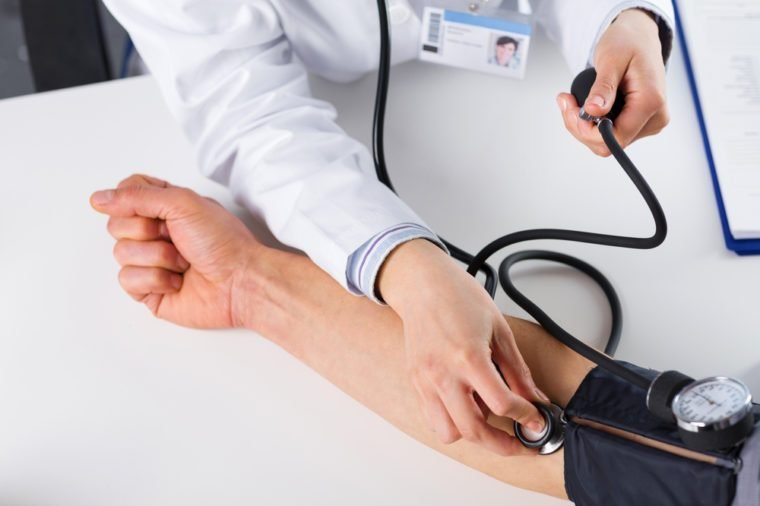 Close Up Of A Female Doctor Checking Blood Pressure Of Male Senior Patient