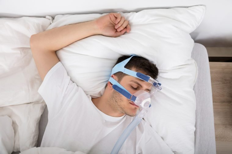 High Angle View Of Man Lying On Bed With Sleeping Apnea And CPAP Machine