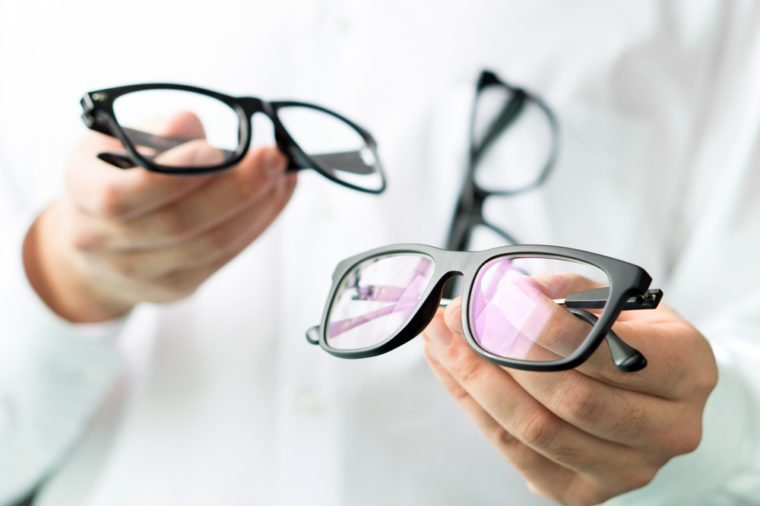Optician comparing lenses or showing customer different options in spectacles. Eye doctor showing new glasses. Professional optometrist in white coat with many eyeglasses.