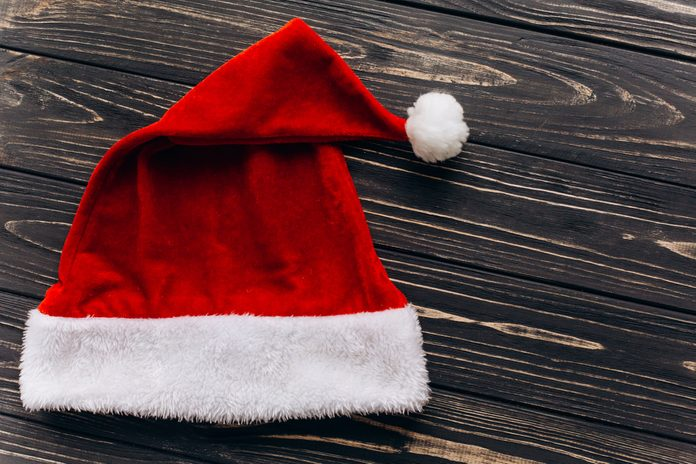 Red Santa Claus hat top lay view, christmas decoration on rustic wooden background, greeting card concept with space for text close-up