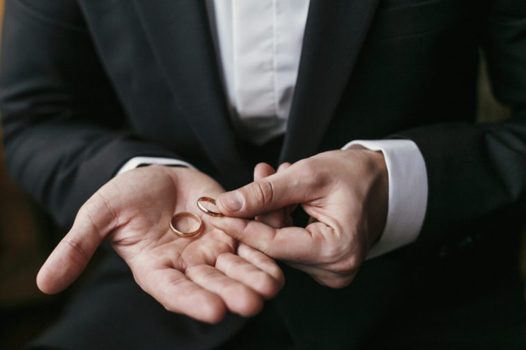 Wedding rings on palm hand. Groom in stylish suit holding golden wedding rings in hands, sitting in the room. marriage or divorce concept