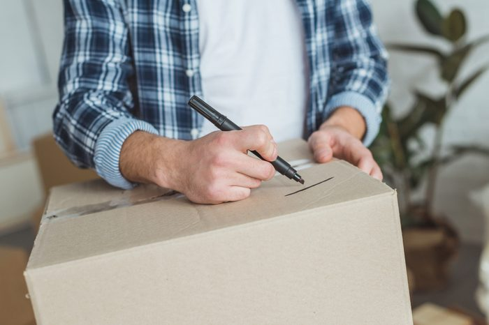 cropped shot of man signing cardboard box for moving home, relocation concept