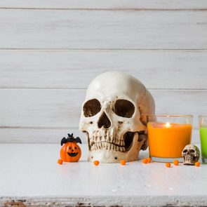 Halloween decorations on table over white wooden background