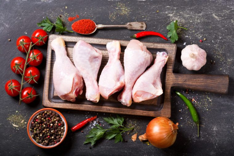 fresh chicken legs on wooden board with ingredients for cooking, top view