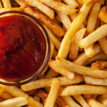 Delicious french fries and ketchup - fast food background, top view, closeup