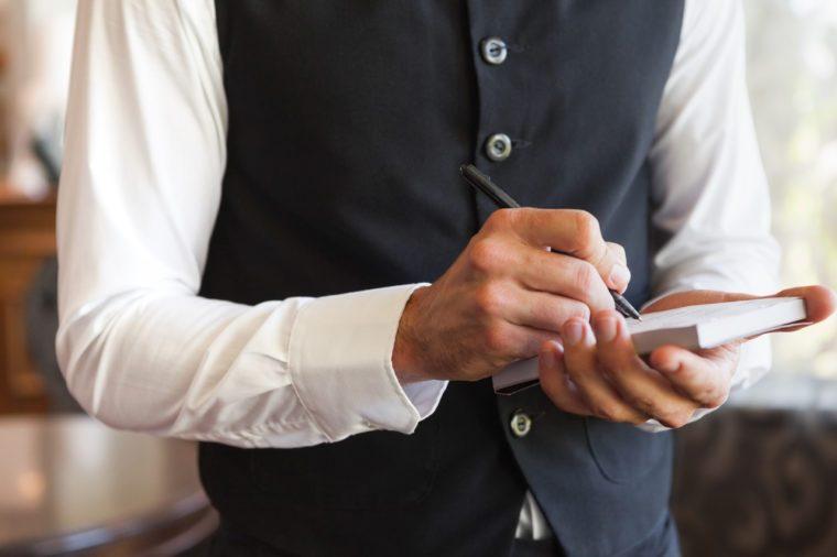 Waiter taking an order wearing a waistcoat in a fancy restaurant