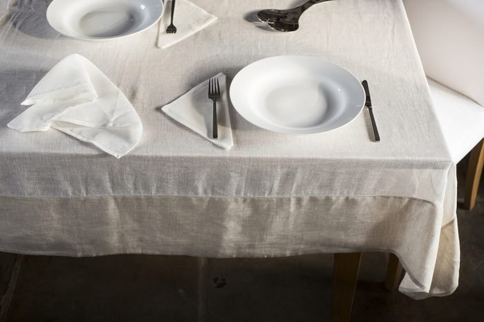 Shot of corner of dining table covered with white linen and with a crumpled table napkin and two sets of dinnerware arranged on opposite sides.