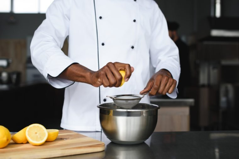cropped image of african american chef squeezing lemons at restaurant kitchen