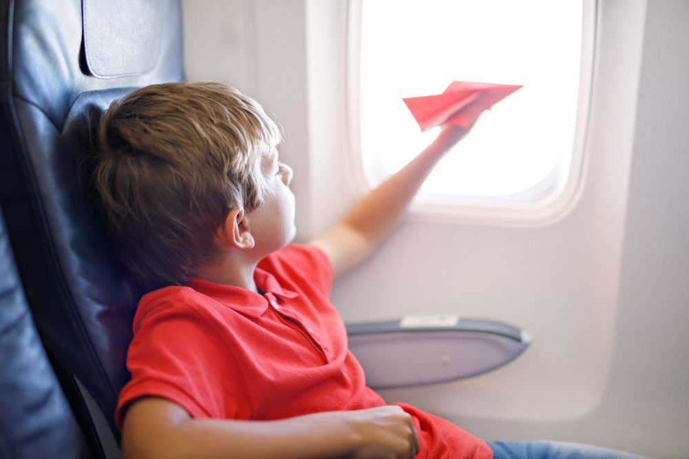 Little kid boy playing with red paper plane during flight on airplane
