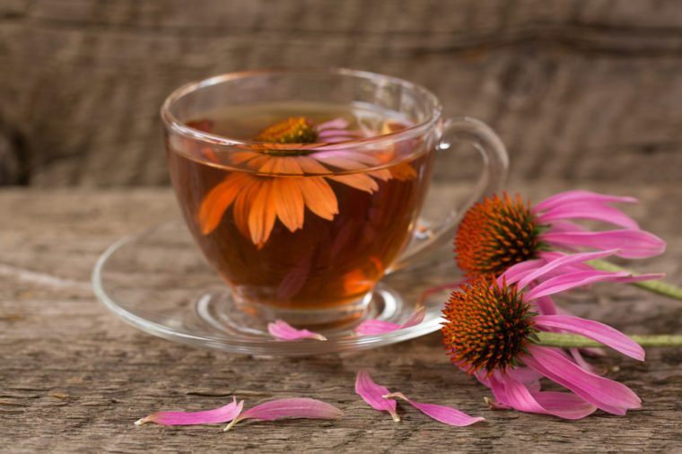 Cup of echinacea tea on old wooden table