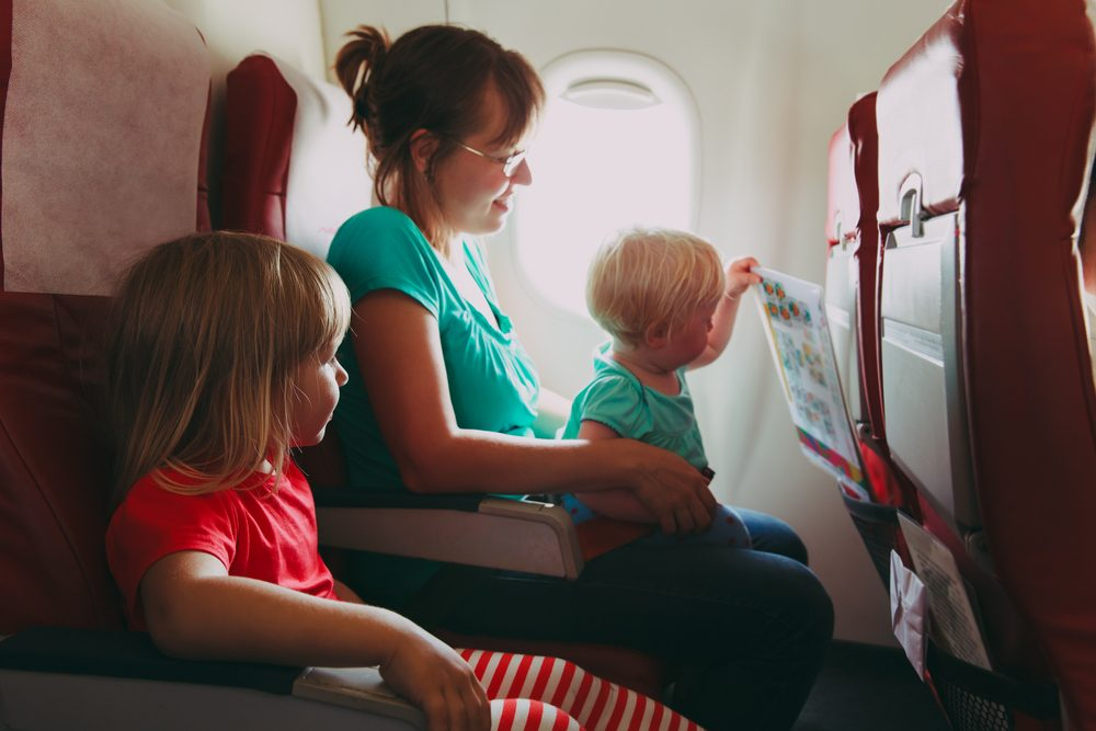 family travel by plane- mother wtih two kids in flight