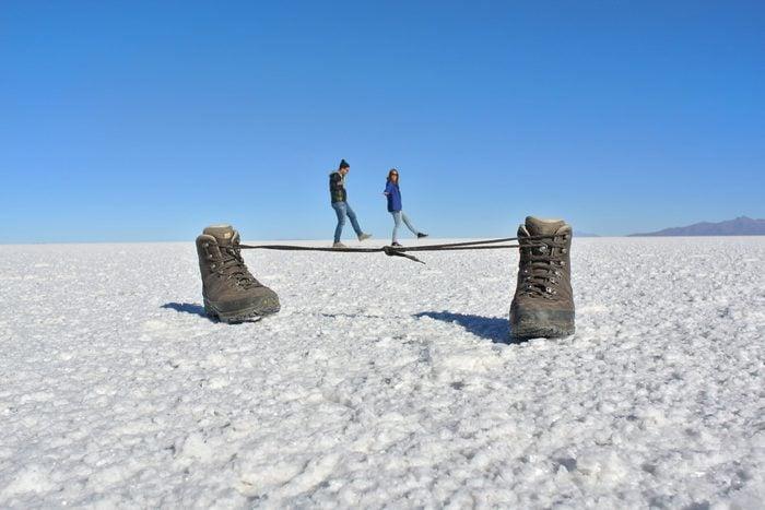 Optical Illusion Of Couple Walking On Shoelaces At Salt Flat