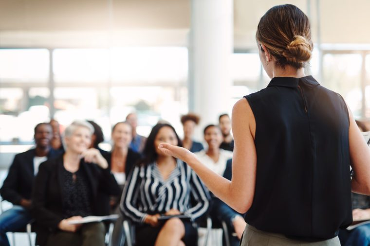 Shot from behind of a young businesswoman delivering a speech during a conference