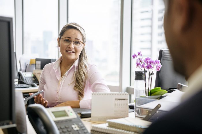 Office worker in her 30s siting at desk and looking towards co-worker, listening and smiling, two people meeting in office