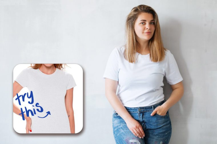 woman in a white tshirt and jeans against a gray wall