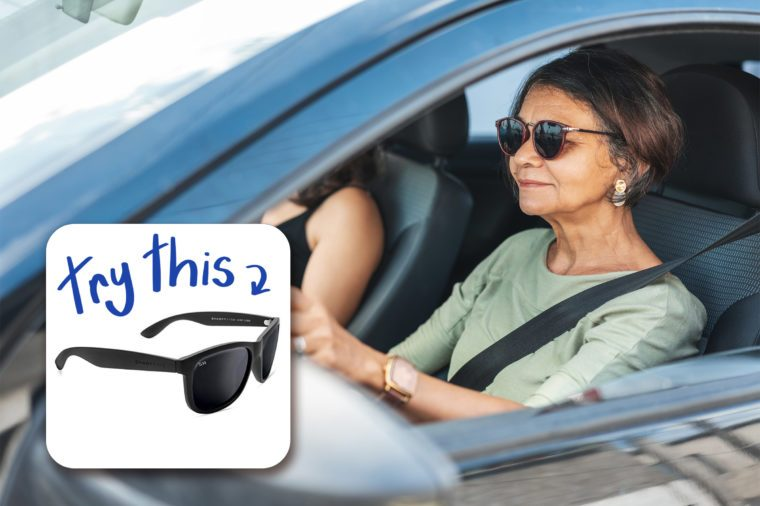 fashionable mature woman driving a car wearing sunglasses
